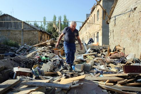 A man walks through rubble as he examines his destroyed house after shelling between Ukrainian forces and pro-Russian separatists in Golmovsky village, Donetsk region. Photographer: Aleksey Filippov/AFP/Getty Images