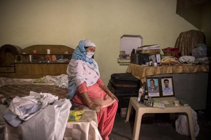 Wife of Covid death, Kuwarsen Singh weeps next to portraits of Kuwarsen Singh (left) and her son Pravinder Kumar.  Kuwarsen singh was sent on an election mission where he was infected with the Covid virus.  Photo taken at her house in Bassi village, Baghpath, Uttar Pradesh, India