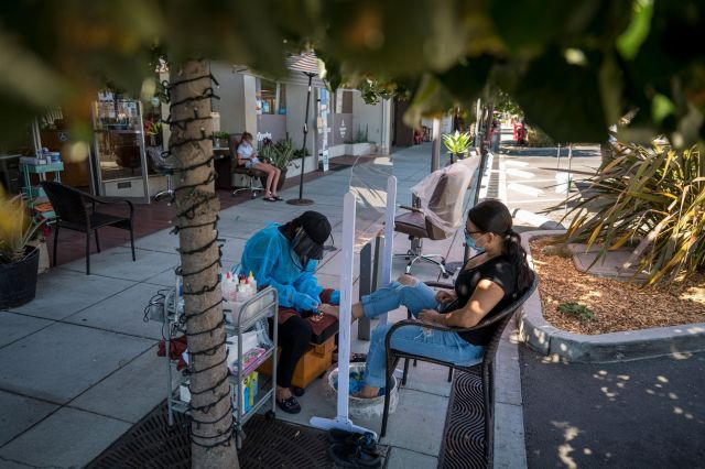 A worker gives a pedicure to a customer outside of a nail salon in Palo Alto, California, on July 28.