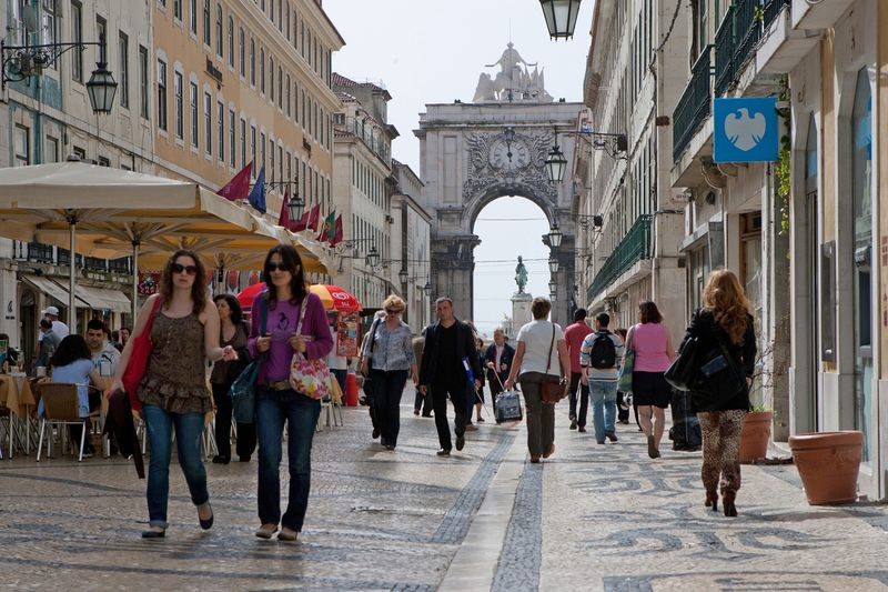 Pedestrians pass by stores lining Augusta street in central Lisbon, Portugal, on Wednesday, April 6, 2011. Portugal plans to tap investors for as much as 1 billion euros ($1.4 billion) today with the clock ticking on Prime Minister Jose Socrates's lame-duck government and a financial rescue that analysts say is all-but inevitable. Photographer: Mario Proenca/Bloomberg