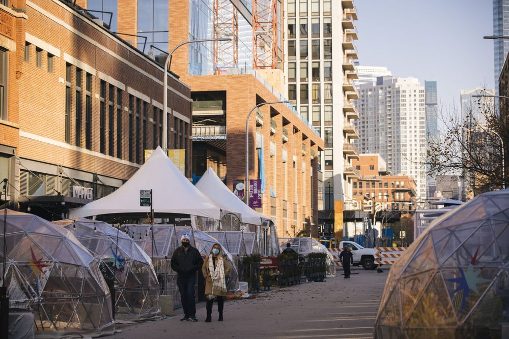 Pedestrians walk past social distancing bubble dining tents at West Fulton Market in Chicago on Nov. 13.