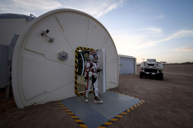 A woman wearing a simulation spacesuit walks out of Mars Base 1.