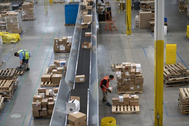 Amazon says it is deploying AI-powered software called Distance Assistant in warehouses that tells workers if they are too close to colleagues (Matt Day/Bloomberg) 1