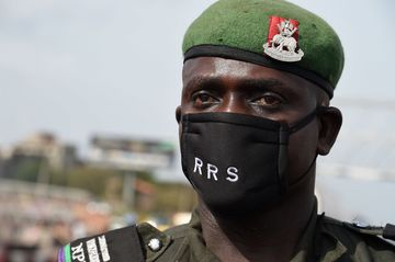 A police officer wears face mask customised from the anti-robbery Rapid Respond Squad as a preventive measure against coronavirus at a in Lagos.