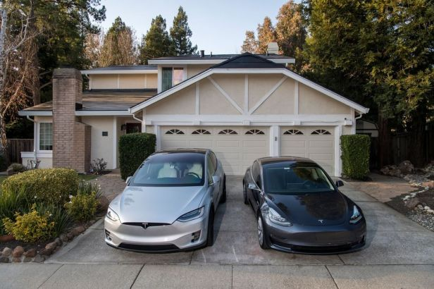 Tesla Model X and Model 3 cars in the driveway of a home with a Tesla Solar Roof in California.