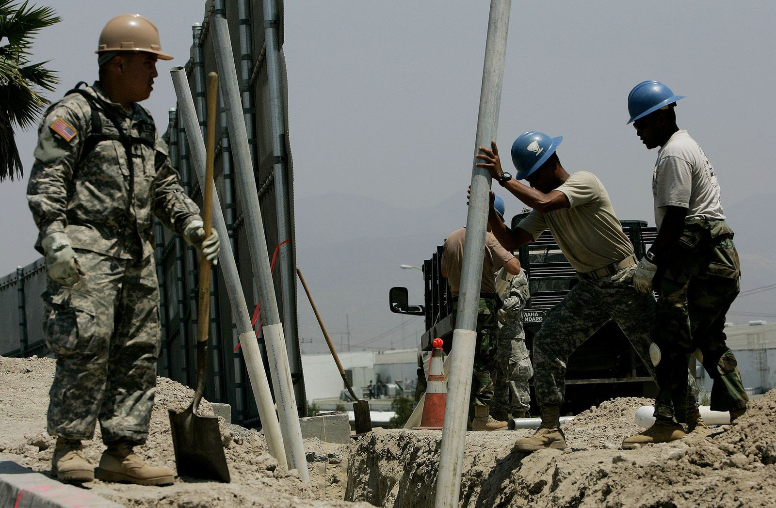 OTAY MESA, CA - JULY 25: Members of the California National Guard prepare to bury plastic pipes for housing electrical wiring along the U.S.-Mexico Border July 25, 2006 in Otay Mesa, California. Approximately 1,000 volunteer Guardsmen are stationed along the California-Mexico border as part of Operation Jump Start, which is providing support for the border patrol agents by repairing fences, improving roads and manning surveillance cameras. The Guard are prohibited from engaging in overt law enforcement. (Photo by Sandy Huffaker/Getty Images)