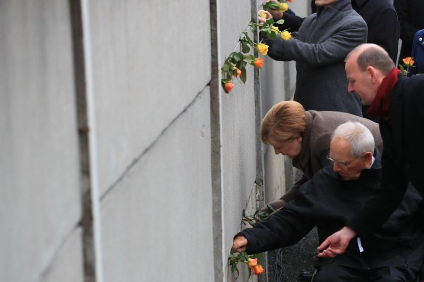 Angela Merkel and Wolfgang Schaeuble place roses into a portion of the wall at Bernauer Strasse on Nov. 9.