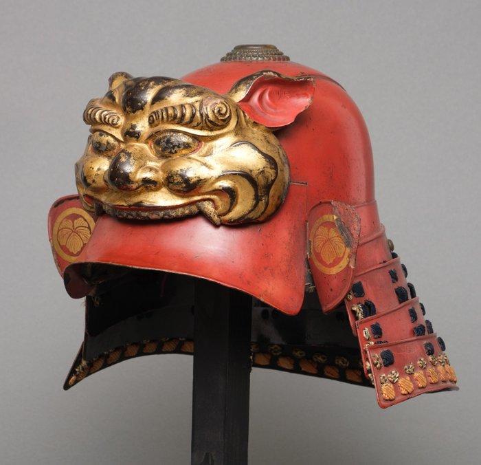 Kabuto - Lacquered metal and wood - Samurai - Red lacquered 18 th century zunari-kabuto helmet with large Shi-shi maedate - Japan - Edo Period (1600-1868)