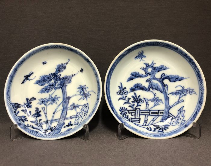 Saucers (2) - Porcelain - Pair - Pine tree, bamboo and blossoms behind a fence - China - Kangxi (1662-1722)