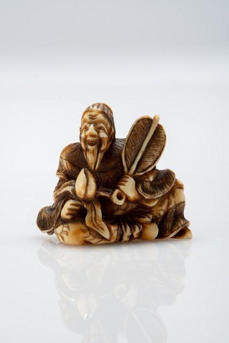 Netsuke - Elephant ivory - Saggio con ventaglio e frutto primo periodo Meiji - Japan - Meiji period (1868-1912)