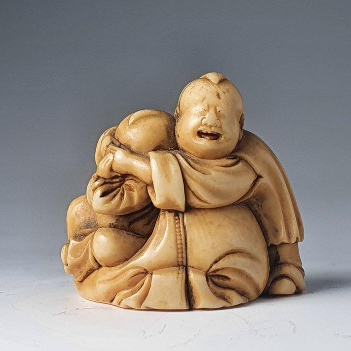 Netsuke - Elephant ivory - Two karako playing on Hotei's bag of riches - Japan - Edo Period (1600-1868)