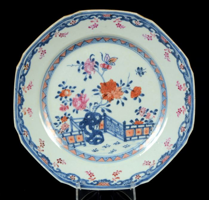 A Chines octagonal plate - Blue and white, Famille rose, Iron red - Porcelain - Garden terrace with flowers, rock, butterflies - NO RESERVE PRICE - Peonia and fence pattern - China - Qianlong (1736-1795)