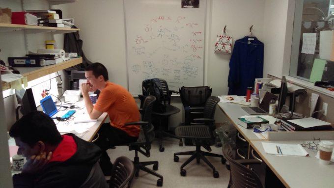 実験スペースの横にあるオフィス。4人で一部屋をシェアしています。「真面目に研究してるふりして!」って言ったらニヤニヤしてる写真になっちゃいました笑