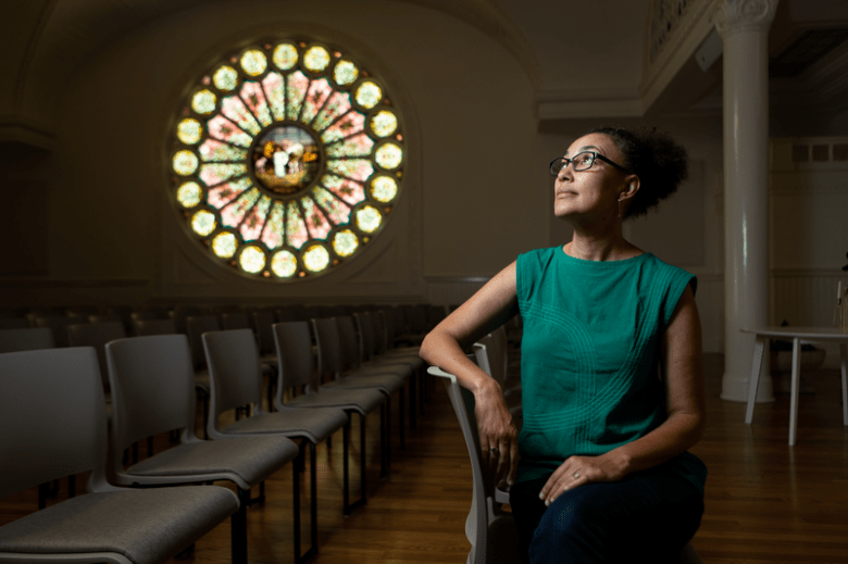 Ariana Makau, the founder of, Nzilani, a stain glass preservation company. Nzilani has worked on stained glass around the Bay Area, including Resurrection Oakland Church. The company's restoration work is featured behind her.