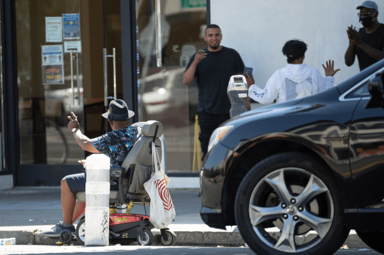 A man on a wheel-chair uses the bike lane to navigate around a crowd on the sidewalk.