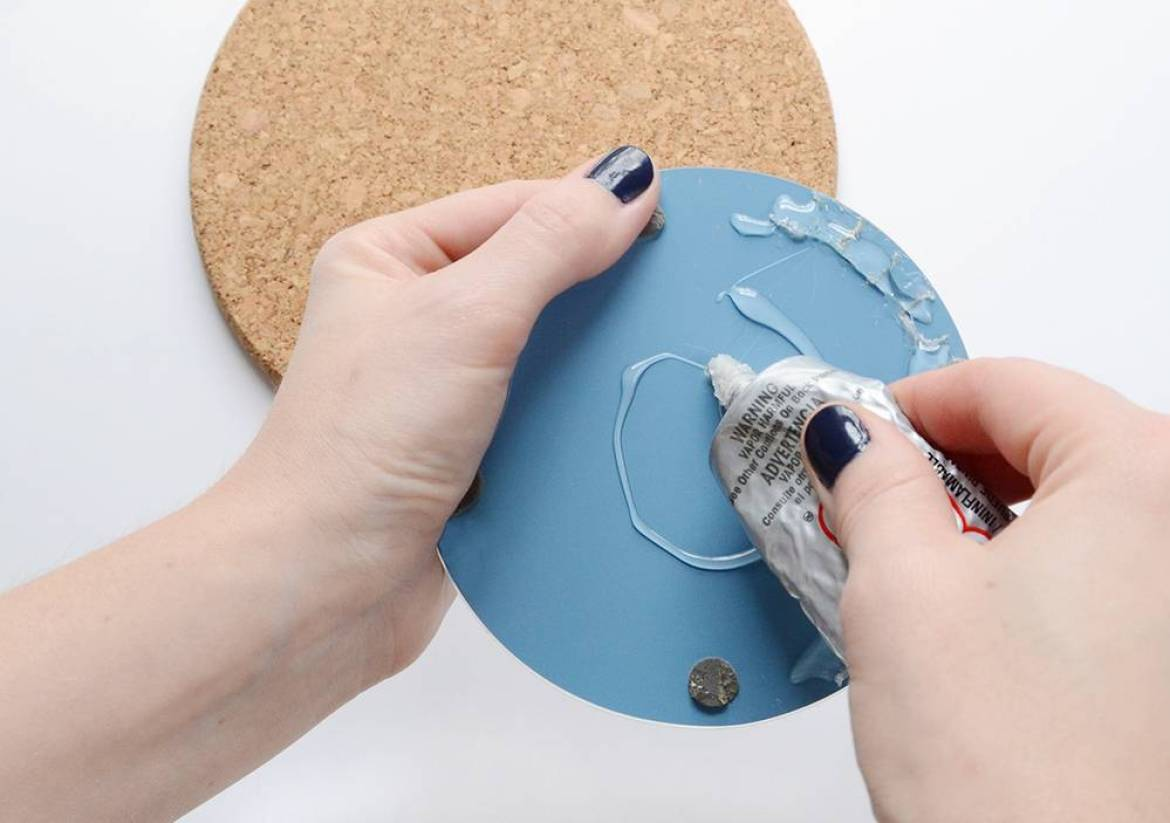 Use glue to secure mirror to cork board
