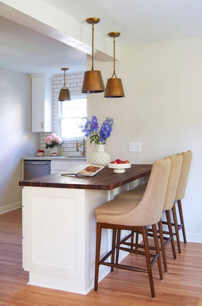 Butcher block countertop on island with white cabinets