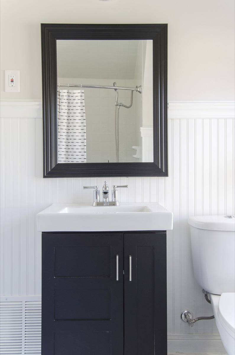 Small bathroom with shallow vanity and black and white color scheme