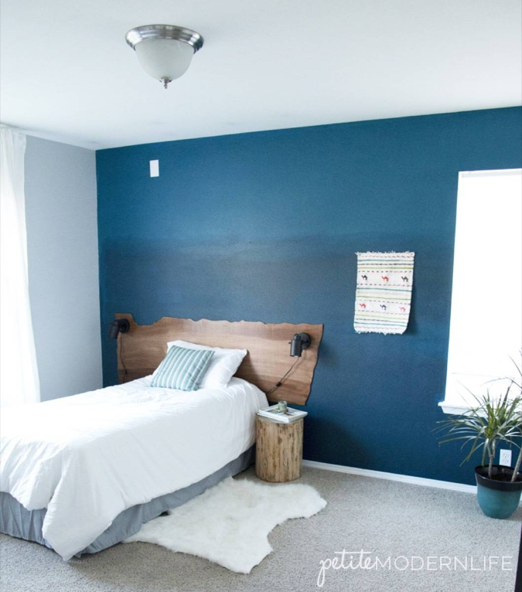 Blue and white bedroom with sheepskin rug on carpeted floor