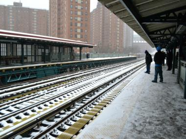 Snow falls on the subway station platform at 125th Street.