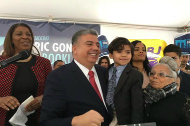 Eric Gonzalez, flanked by Public Advocate Letitia James (left), his son Cole, and his mother Carmen, celebrates the launch of his campaign for Brooklyn District Attorney Wednesday.