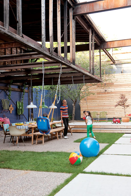 This Toronto residence seamlessly integrates spaces for children and adults. Architect John Tong made the courtyard an extension of his house, with a big table that hosts parties, a stage for impromptu performances, and part of an old loft overhead that will one day become a treehouse for the children. Photo by Stacey Brandford.   Photo by: Christopher Wahl