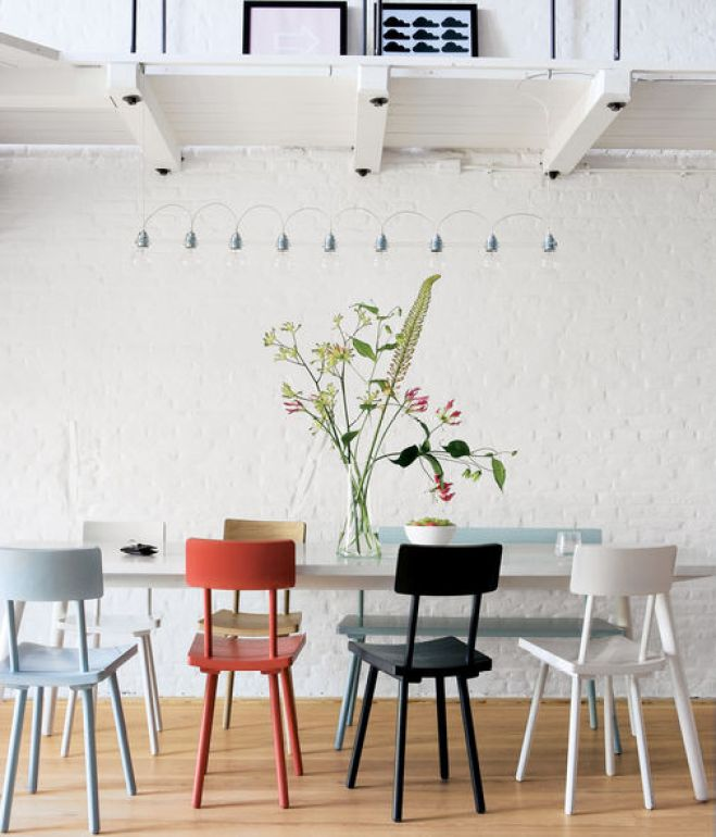"""<br /><br /><br /><br /><br /><br /> Piet Hein Eek's wooden chairs add a touch of color to the monochromatic apartment. """"I'm a fan of simple modern furniture, with a twist,"""" says Carr. """"I wanted to buy everything from Piet Hein Eek."""" Photo by Rene Mesman.<br /><br /><br /><br /><br /><br />"""