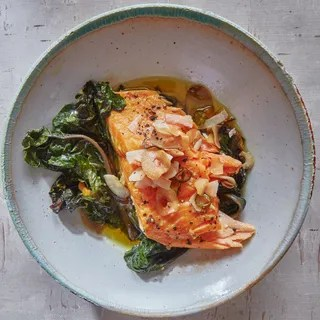 Salmon and greens topped with coconut flakes in a bowl against a light greywhite background.