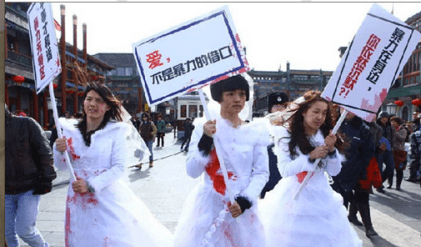 "Li (left) and Wei (right) dress up in bloodstained wedding gowns to raise awareness on domestic violence in China. Their signs: ""Why are you still silent about intimate  violence around you?"" and ""Love is not an excuse for violence"". (Source: artintern.net)"