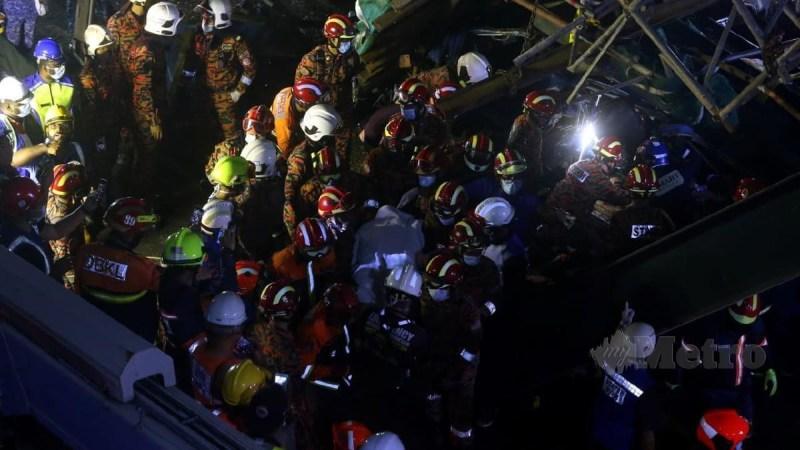 PASUKAN penyelamat membawa keluar mayat mangsa selepas van kilang dinaiki dihempap runtuhan jejambat, hari ini. FOTO HAIRUL ANUAR ABD RAHIM