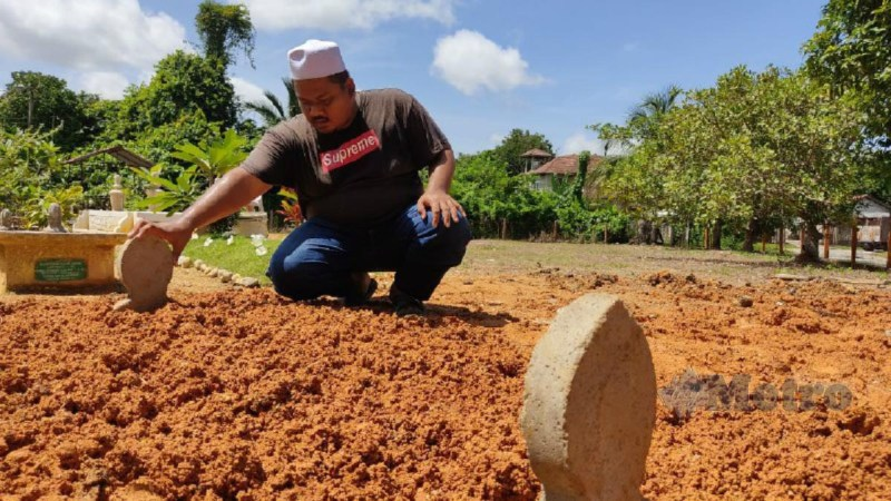 Mohd Zaid di kubur Allahyarham Siti Nur Surya di Kampung di Kampung Beladau Selat, Kuala Terengganu. Foto Zaid Salim