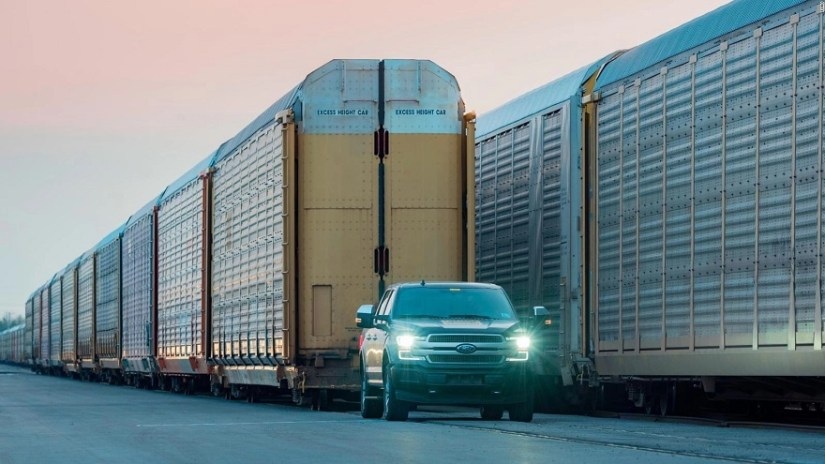 The new Ford F150 shows its power by dragging a train.