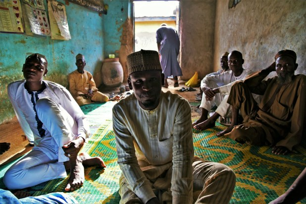 Members of the Miyetti Allah Cattle Breeders Association sit in a sparsely decorated room, sunlight streaming in through the door behind them.