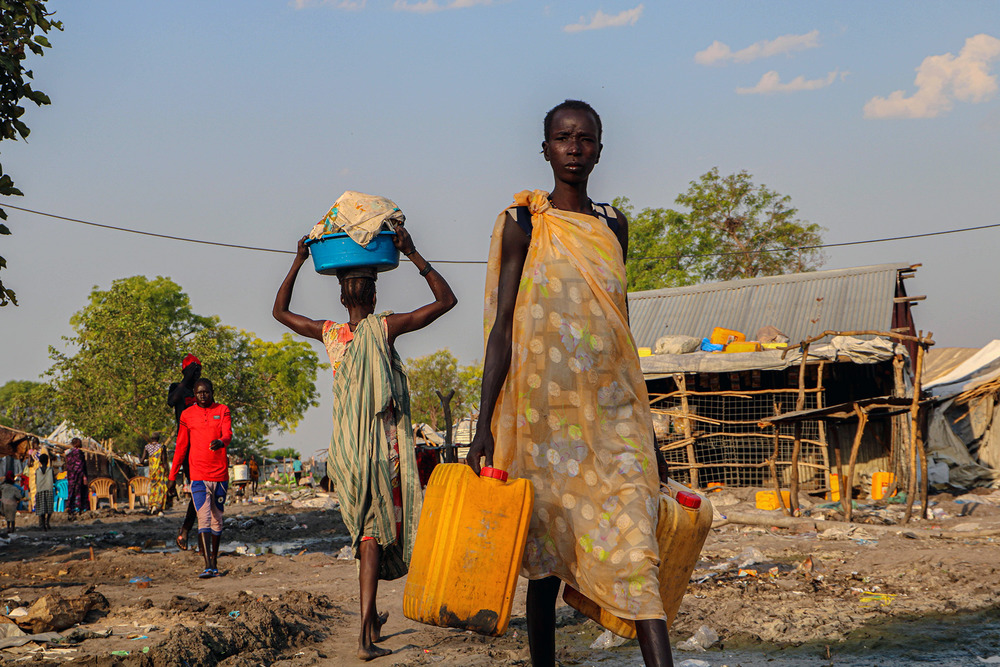 A woman walks towards the camera carrying cans of water.