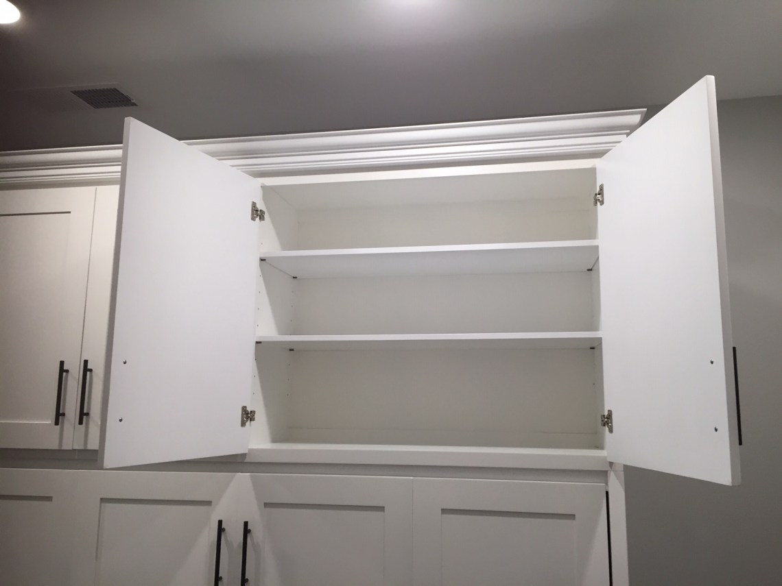 Horizontal full size Murphy bed cabinet with detail of top cupboard. Adjustable shelves