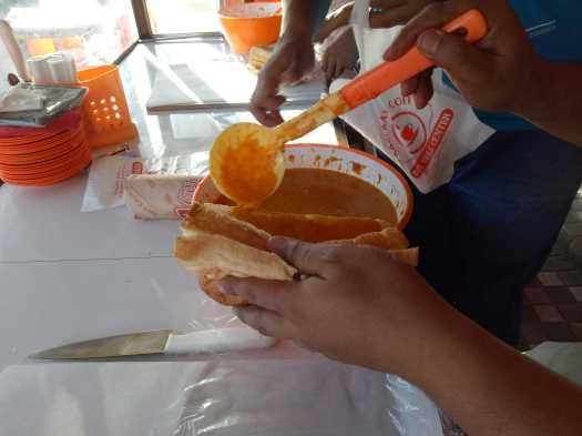 Tampak seorang pekerja bagian pelayanan penjualan sedang mengolesi sele pada roti yang telah dibelah menggunakan sendok khusus. (foto: koleksi pribadi)