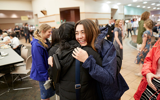 Two sister missionaries hug each other in the cafeteria of the missionary training center