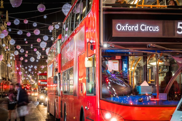 A red double decker bus drives down Oxford Street, London, with Christmas lights hanging overhead