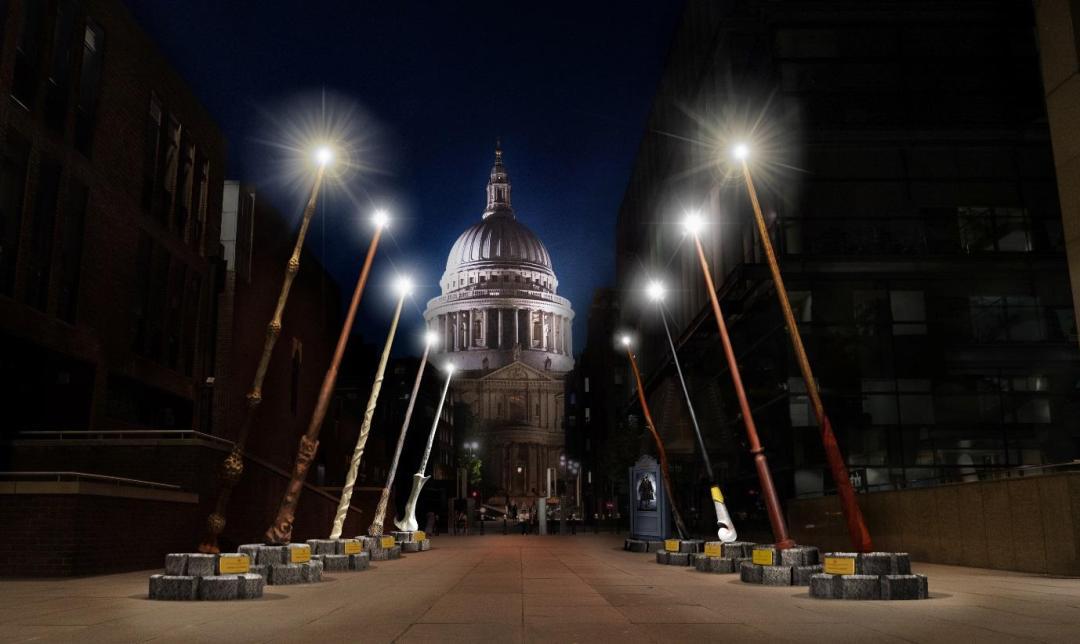 Obrovské repliky hůlek po stranách cesty od Milennium Bridge ke katedrále sv. Pavla. Konce hůlek, které směřují k obloze, svítí. Za hůlkami je kupole katedrály sv. Pavla za noci.