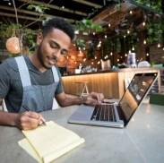Hombre feliz haciendo los libros en un restaurante usando una computadora portátil - conceptos de pequeñas empresas