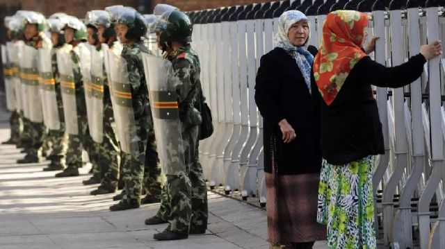 An ethnic Uighur women looks through a security fence to the Grand Bazaar which remains closed as Chinese soldiers look on in Urumqi, in Chinese farwest Xinjiang region on July 9, 2009. - AFP/File pic