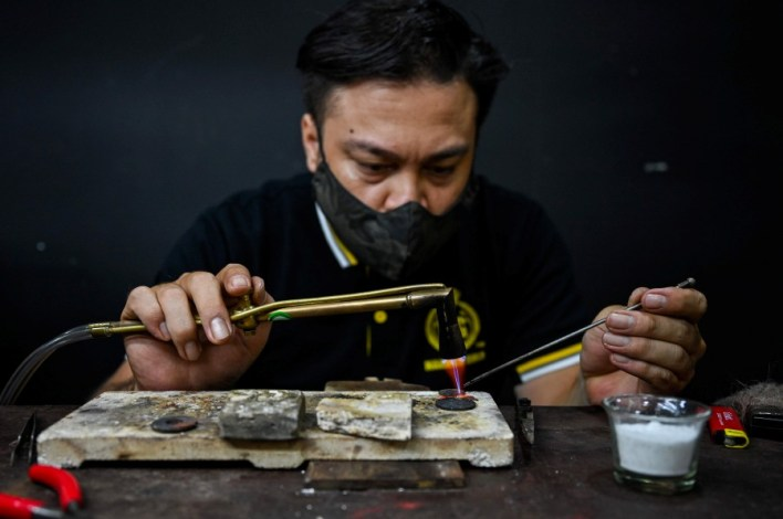 A jewellery craftsman heating a decoration with a torch at the Makmur Gold workshop in Kota Baru in Kelantan. - AFP pic