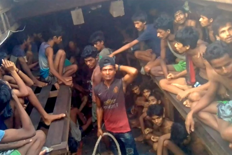 This video grab taken on December 4, 2020 from an AFPTV video shows a Burmese smuggler (C) along with Rohingya refugees in a boat in Chakmarkul on August 26, 2020. -AFP pic/Handout