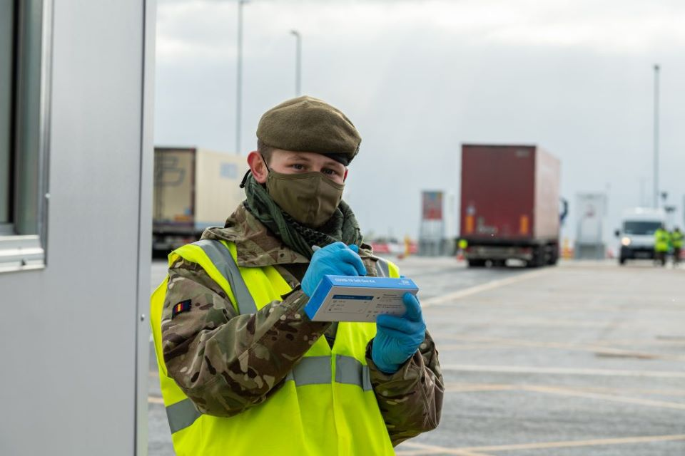 Private Ollie Wilson writes on a COVID-19 testing kit. He wears a face mask and camo uniform.