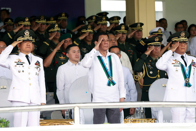 CHANGE OF COMMAND. President Rodrigo Duterte (center), retired General Eduardo Año (left), and new AFP chief Lieutenant General Rey Guerrero (right) salute the troops during the AFP change of command ceremony at Camp Aguinaldo on October 26, 2017. Malacañang photo