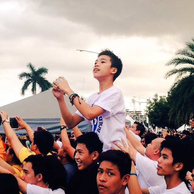 A young boy perches on top of his brother while waiting for the papal motorcade enter the Mall of Asia (MOA) Arena