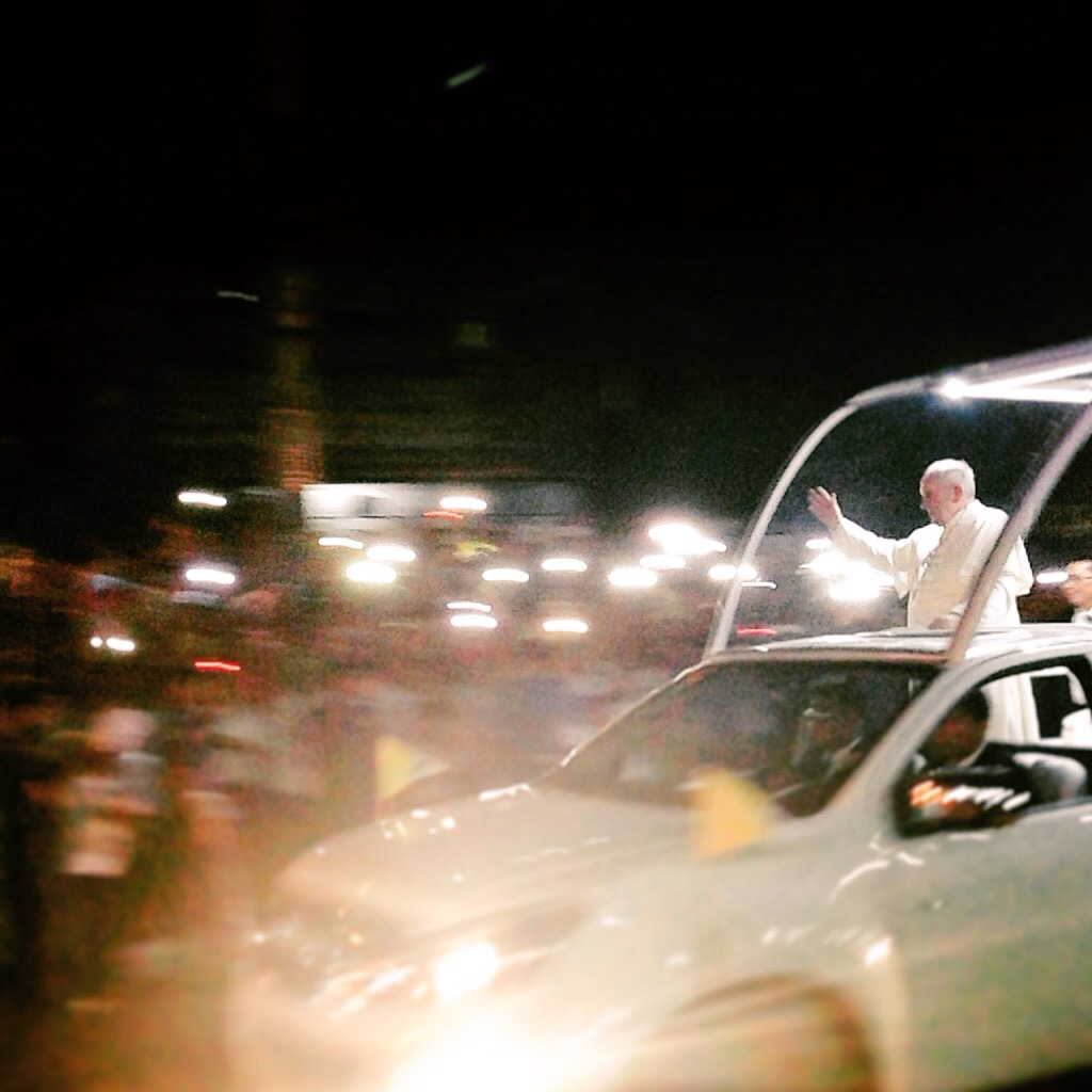 Pope Francis waves to the crowds during his arrival in Manila