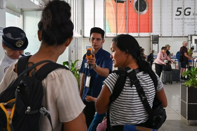 SCREENING. Airport personnel check the temperature of a passenger at the departure area of the Ninoy Aquino International Airport on February 23, 2020. Photo by Romeo Gacad/AFP