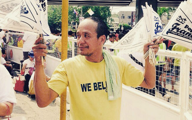 """The man said he made the flags for Pope Francis after he saw the pontiff speaking to a large crowd. """"Ginawa ko 'to. May kasamang 'We Love' dapat yan."""" (I made these flags. I was supposed to add 'We love' before his name.)"""