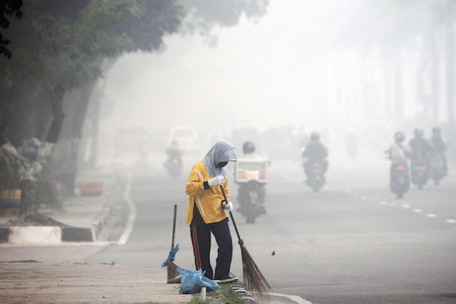 ASAP RIAU. Seorang pekerja membersihkan jalan di tengah kabut asap yang menyelimuti Pekanbaru, Riau, 6 Oktober 2015. Pemerintah Riau mengatakan ada 40.000 orang menderita ISPA karena kabut asap yang telah berlangsung lebih dari dua bulan. Foto oleh Rony Muharrman/EPA